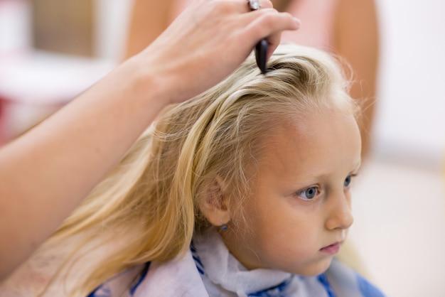 Kleines mädchen, das einen haarschnitt am salon tut.