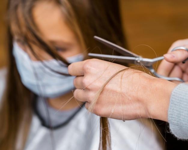 Kleines mädchen, das einen haarschnitt erhält, während es medizinische maske trägt
