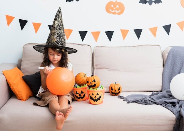 Kleines mädchen, das einen halloween-ballon zeichnet