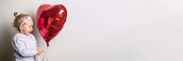 Kleines mädchen, das einen herzluftballon hält und es auf einem hellen hintergrund betrachtet. konzept für valentinstag, geburtstag. banner.