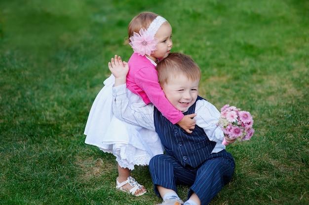 Kleines mädchen, das einen jungen mit einem blumenstrauß von blumen im park umarmt