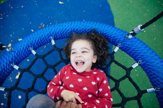 Kleines mädchen, das einen kitzelangriff im park hat