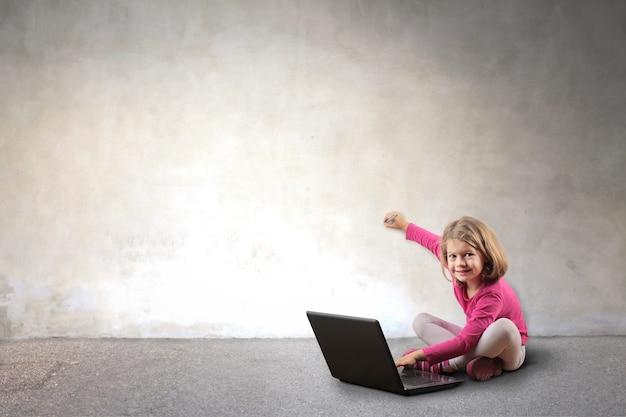 Kleines mädchen, das einen laptop verwendet und auf eine wand schreibt