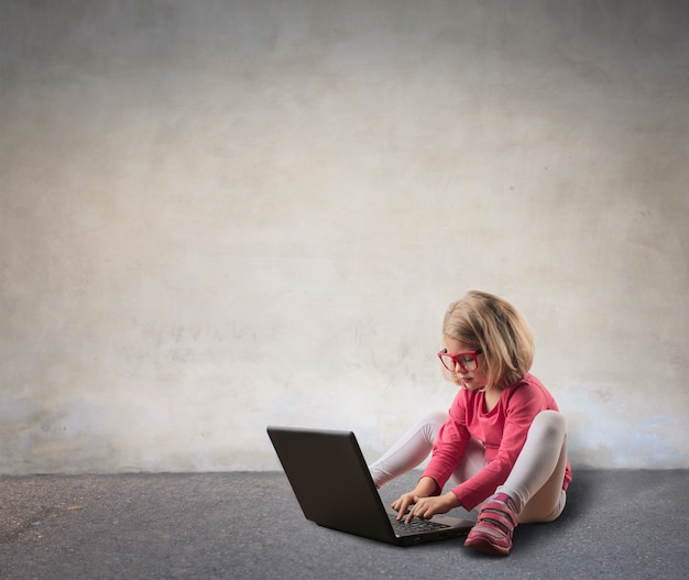 Kleines mädchen, das einen laptop verwendet