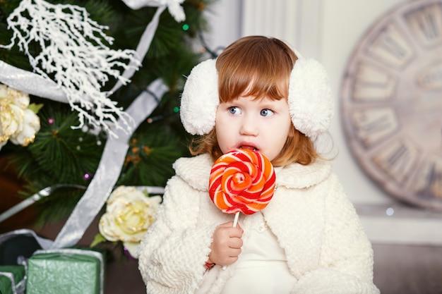 Kleines mädchen, das einen lutscher isst. porträt eines lustigen kleinen mädchens in ohrenschützern mit einer köstlichen süßigkeit in den händen. weihnachts- und neujahrskonzept