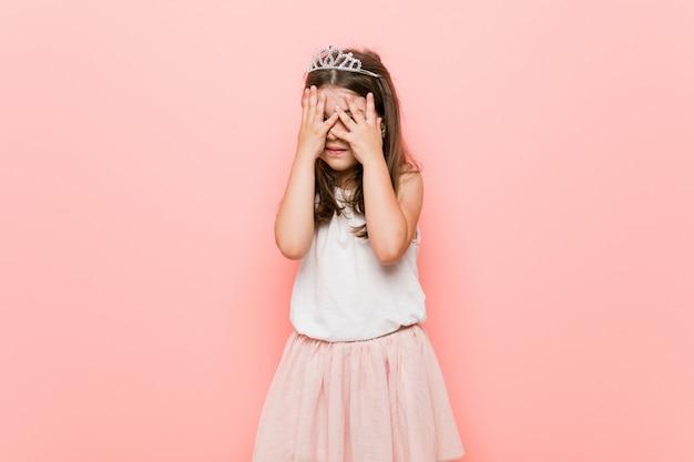 Kleines mädchen, das einen prinzessinblick trägt, blinzeln durch die verängstigten und nervösen finger