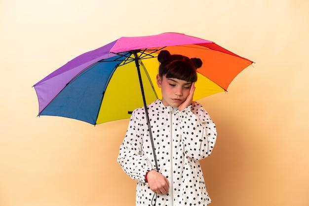 Kleines mädchen, das einen regenschirm lokalisiert auf beige mit kopfschmerzen hält