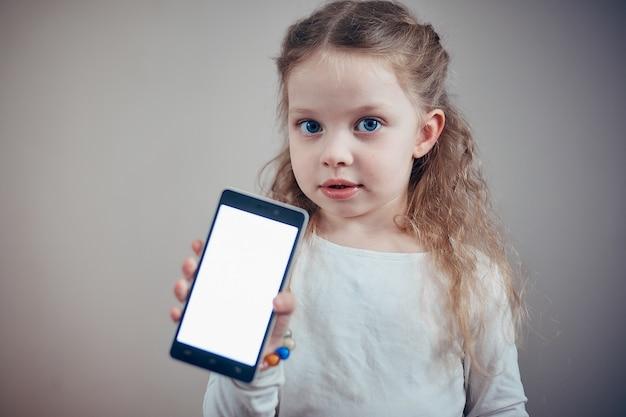Kleines mädchen, das einen smartphone mit einem weißen schirm hält