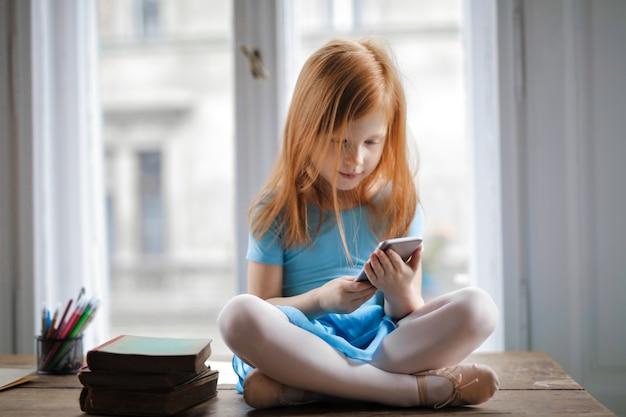 Kleines mädchen, das einen smartphone verwendet