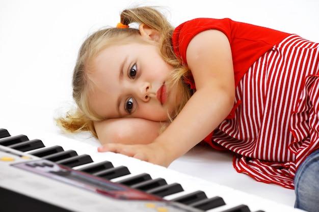 Kleines mädchen, das einen synthesizer spielt