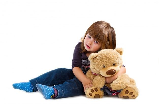 Kleines mädchen, das einen teddybären hält