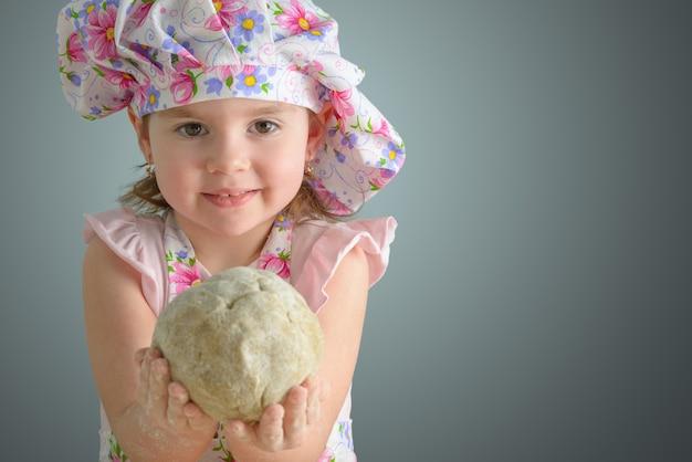 Kleines mädchen, das einen teigball hält