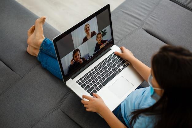 Kleines mädchen, das einen videoanruf mit dem laptop macht