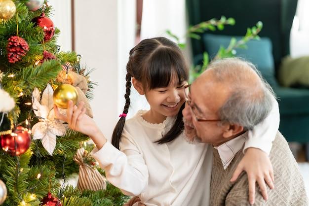 Kleines mädchen, das einen weihnachtsbaum mit ihrem großvater schmückt