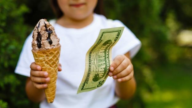 Kleines mädchen, das eiscreme gegen dollar austauscht