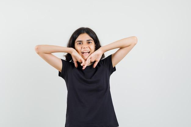 Kleines mädchen, das ellbogen im schwarzen t-shirt streckt und fröhlich, vorderansicht schaut.