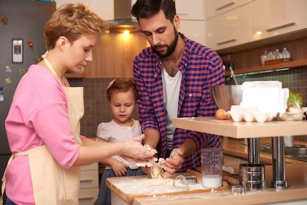 Kleines mädchen, das eltern in der küche hilft
