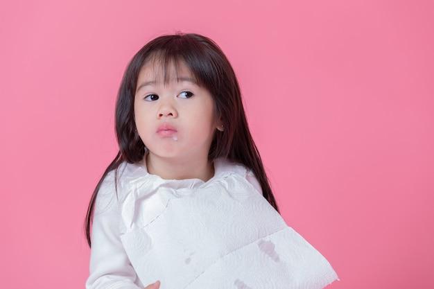 Kleines mädchen, das essen durch plastiklöffel mit einem taschentuch isst, das in eine schürze in rosa wand gemacht wird.
