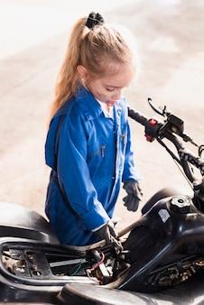 Kleines mädchen, das fahrrad mit schlüssel repariert