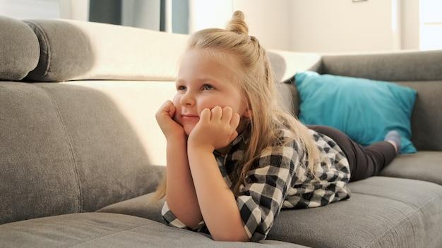 Kleines mädchen, das fernsehen zu hause liegt auf der couch. ein kind schaut sich cartoons an