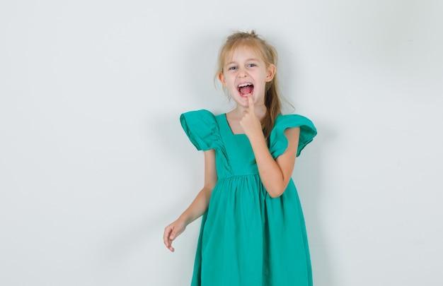 Kleines mädchen, das finger auf ihrer lippe in der vorderansicht des grünen kleides hält.