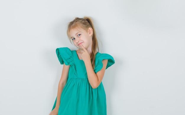 Kleines mädchen, das finger auf kinn im grünen kleid hält und hübsch aussieht. vorderansicht.