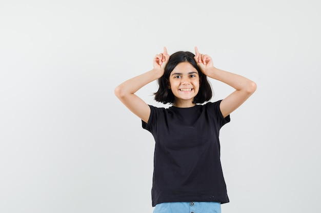 Kleines mädchen, das finger über kopf als stierhörner im schwarzen t-shirt, in den shorts und in der lustigen vorderansicht hält.
