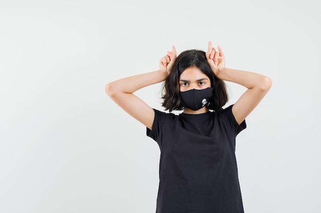 Kleines mädchen, das finger über kopf als stierhörner im schwarzen t-shirt, in der maske und in der lustigen vorderansicht hält.