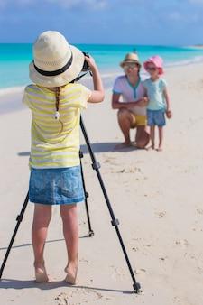 Kleines mädchen, das foto von ihrem vati und von schwester am strand macht