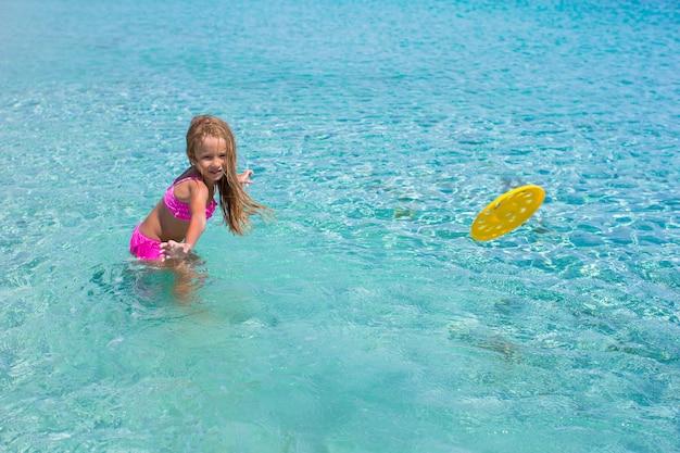 Kleines mädchen, das frisbee auf tropischem weißem strand während der ferien spielt