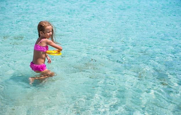 Kleines mädchen, das frisbee während der tropischen ferien im meer spielt
