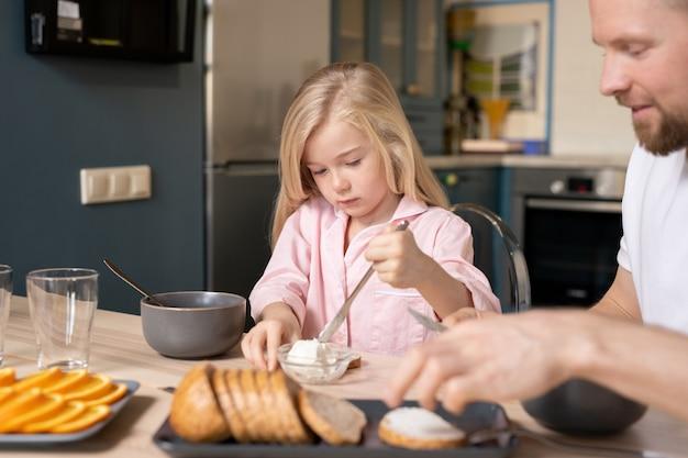Kleines mädchen, das frische butter nimmt, um sie in schüssel mit haferbrei zu setzen, während es am tisch sitzt und mit ihrem vater in der küche frühstückt