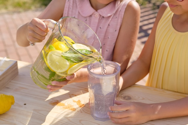 Kleines mädchen, das frische kühle hausgemachte limonade in plastikglas gießt, während getränke mit ihrem freund durch stand am heißen sommertag verkauft