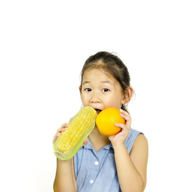 Kleines mädchen, das frischen orange und süßen mais anhält