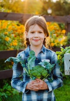 Kleines mädchen, das frisches organisches gemüse hält