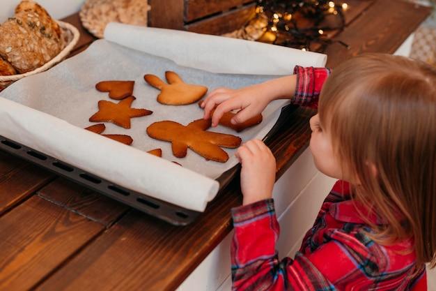 Kleines mädchen, das gebackene weihnachtsplätzchen prüft