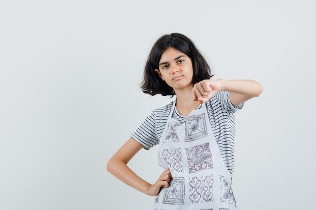Kleines mädchen, das geballte faust im t-shirt, in der schürze zeigt und selbstbewusst aussieht