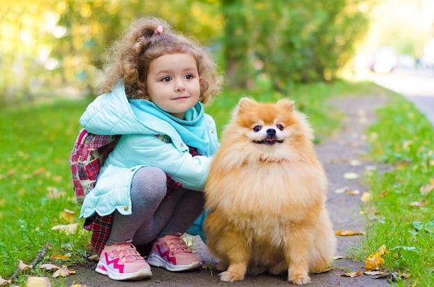 Kleines mädchen, das geht, einen hund pommerschen spitz im herbstpark trainierend.