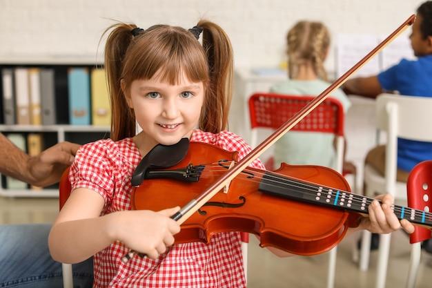 Kleines mädchen, das geige an der musikschule spielt
