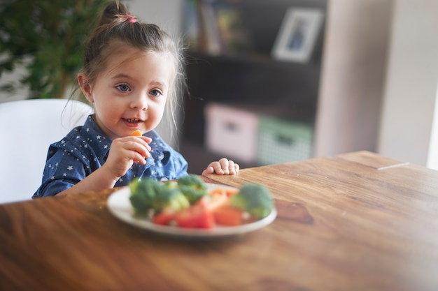 Kleines mädchen, das gemüse isst