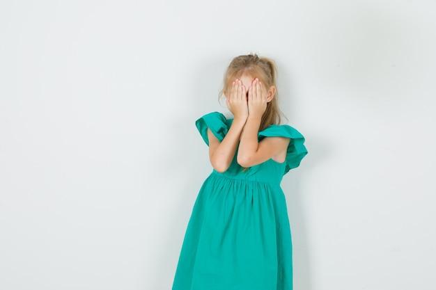 Kleines mädchen, das gesicht mit händen im grünen kleid bedeckt und schüchtern schaut. vorderansicht.