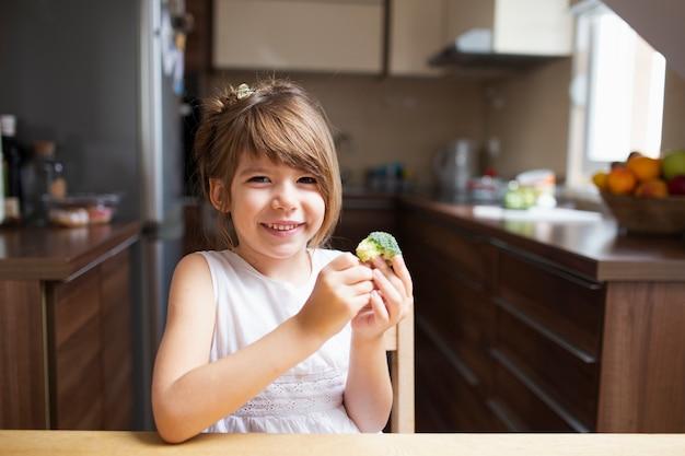 Kleines mädchen, das gesunden imbiß isst