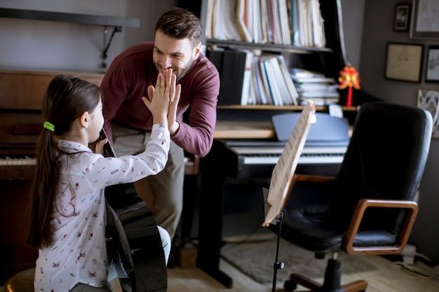 Kleines mädchen, das gitarre mit ihrem musiklehrer in der rustikalen wohnung spielt