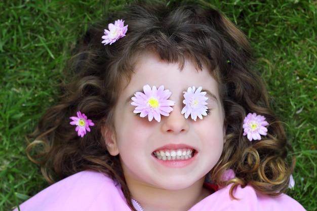 Kleines mädchen, das gras daisiy blumen in augen legt