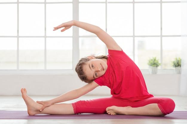 Kleines mädchen, das gymnastik macht und sich streckt