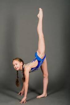 Kleines mädchen, das gymnastik mit reifen, ball und split lokalisiert auf grauem hintergrund, studio tut