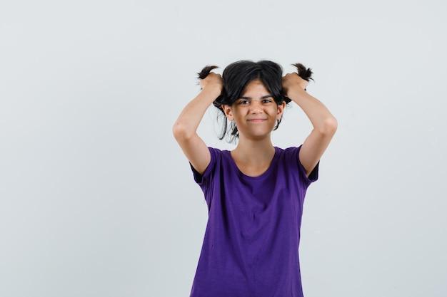 Kleines mädchen, das haarsträhnen im t-shirt hält und lustig aussieht.