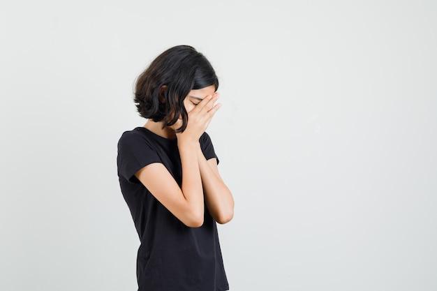 Kleines mädchen, das hände auf gesicht im schwarzen t-shirt fasst und traurig aussieht. vorderansicht.