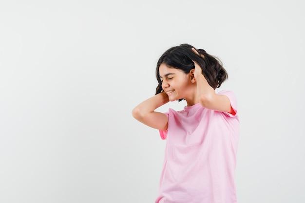 Kleines mädchen, das hände im haar im rosa t-shirt hält und glückselig aussieht. vorderansicht.