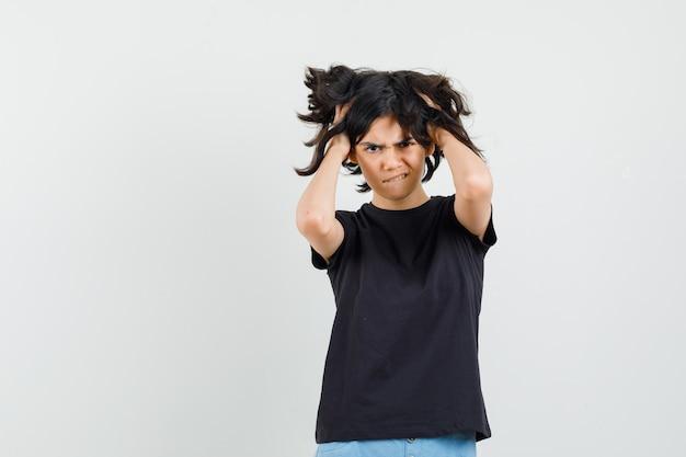 Kleines mädchen, das hände im haar im schwarzen t-shirt, in den kurzen hosen und in der verzweifelten vorderansicht hält.